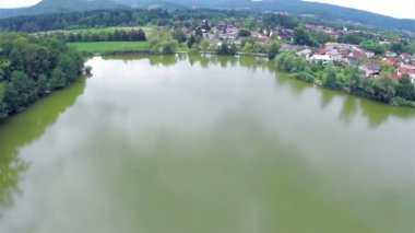 Aerial view of small green lake outskirt of town — Stockvideo
