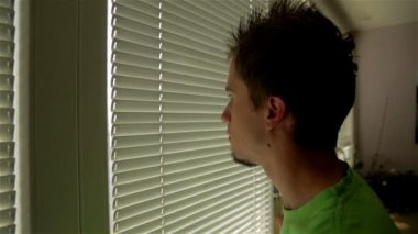 Man looking through roller blind — Stock Video