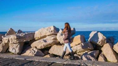 Woman walking on rocky beach — Stock Video
