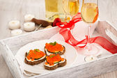 Heart shaped toasts  with red caviar and white wine — Stock Photo