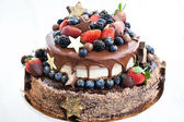 Chocolate cake with icing, decorated with fresh fruit — Stock Photo
