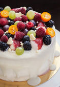 White chocolate cake decorated with fresh berries and fruits — Stock Photo