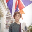 Outdoor shot of a teenager boy in front of the british union jac — Stock Photo #53573347