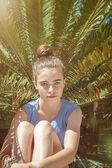 Portrét dospívající dívky, sedící před palmu — Stock fotografie