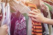 Close up of a hand, looking on a flea market for clothes — Stock Photo