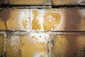 Faded white heart symbol on a grungy yellow brick wall — Stock Photo