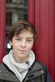 Portrait of a beautiful teenage boy in front of a red door — Stock Photo