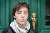 Portrait of a beautiful teenage boy in front of a green door — Stock Photo