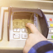 Close-up of hand entering PIN, pass code on ATM, bank machine ke — Stock Photo #67914533