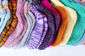A  row of multicolored hand-knitted baby socks — Stock Photo