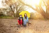 Two teenager with umbrella sitting on a dirty beach with sun in — Stock Photo