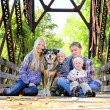 Family of Four People and Dog Sitting On Bridge in Autumn — Stock Photo #53947917