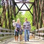 Happy Family of Four People Walking Dog Outside on Bridge — Stock Photo #53947983