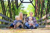 Family of Four People and Dog Sitting On Bridge in Autumn — Stock Photo