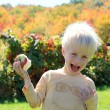 Happy Laughing Child Eating Apple at Orchard — Stock Photo #54764913