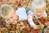 Two Young Children Playing in Fall Leaf Pile — Stock Photo
