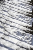 Shadows of wrought ironwork on snow — Stock Photo