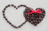 Two hearts of coffee beans on a textured bag — Stock Photo