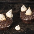 Chocolate pumpkin cupcake, decorated with meringue ghosts — Stock Photo #53542915