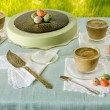 Easter table with tea matcha cheesecake and white coffee on background of green grass — Stock Photo #64709667