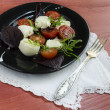 Italian caprese salad with fresh basil leaves, tomato and  mozzarella  on red wooden table. — Stock Photo #66957975