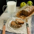 Homemade bread with apples in wrapping paper and glass of milk on plate — Stock Photo #66979983