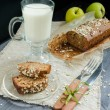 Homemade bread with apples in wrapping paper and glass of milk on white plate — Stock Photo #66979999