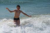 Boy playing with waves in sea — Stock Photo