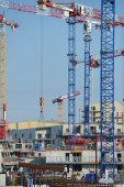 Construction cranes and site against a blue sky — Stock Photo
