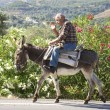 Old man riding a donkey on the street on Crete — Stock Photo #58146825