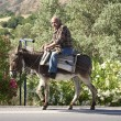 Old man riding a donkey on the street on Crete — Stock Photo #58146873