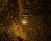 Old light bulb in cave — Stock Photo