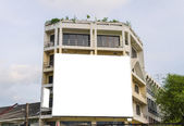 Blank billboard on building in city view background — Stock Photo