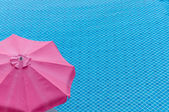 Red umbrella on swimming pool in summer — Stock Photo