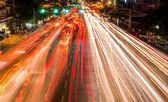 Light streams from ongoing traffic in business district road — Stock Photo