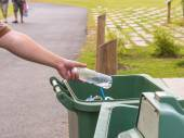 Hand throwing bottle in trash cans — Stock Photo