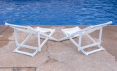 Luxury swimming pool with white deckchairs. — Stock Photo