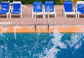Luxury swimming pool with white deckchairs — Stock Photo