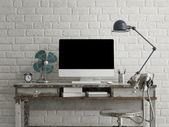 Копируйте монитор на столе, белом кирпичном фоне — Стоковое фото