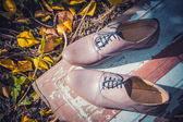 Women's shoes lie on a wooden board near the yellow leaves — Stock Photo