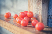 Tomatoes in the rain on the wooden background — Stockfoto