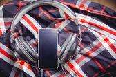 Téléphone et le casque sur une chemise, écouter de la musique — Photo