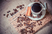 Scattered grains of coffee in a cup on a wooden background — Stock Photo