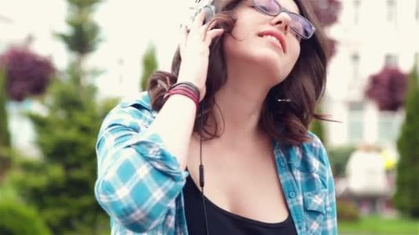 Hermosa chica escuchando música en auriculares estéreo — Vídeo de stock