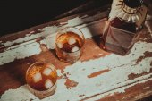 Two glasses of whiskey vintage photo, a bottle on the bar — Stock Photo
