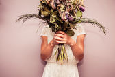 Young woman holding bouquet of dead flowers — Stock Photo