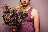 Young man holding bouquet of dead flowers — Stockfoto