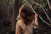 Young woman standing in a clearing of the forest  — Stock Photo