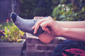 Young woman putting on socks outside — Stock Photo