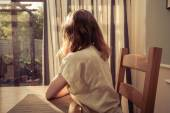 Young woman sitting at table and looking out the window — Stock Photo